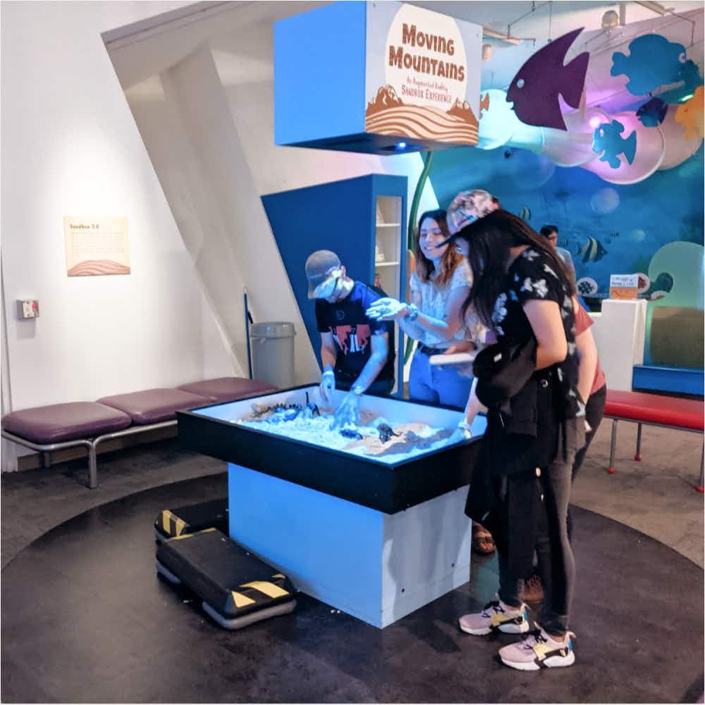 Students examining interactive digital exhibit