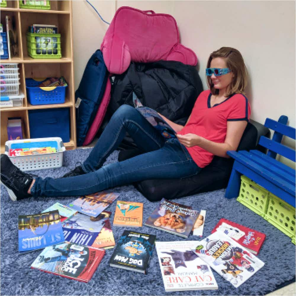 Women sitting on the ground reading children's books with 3d glasses