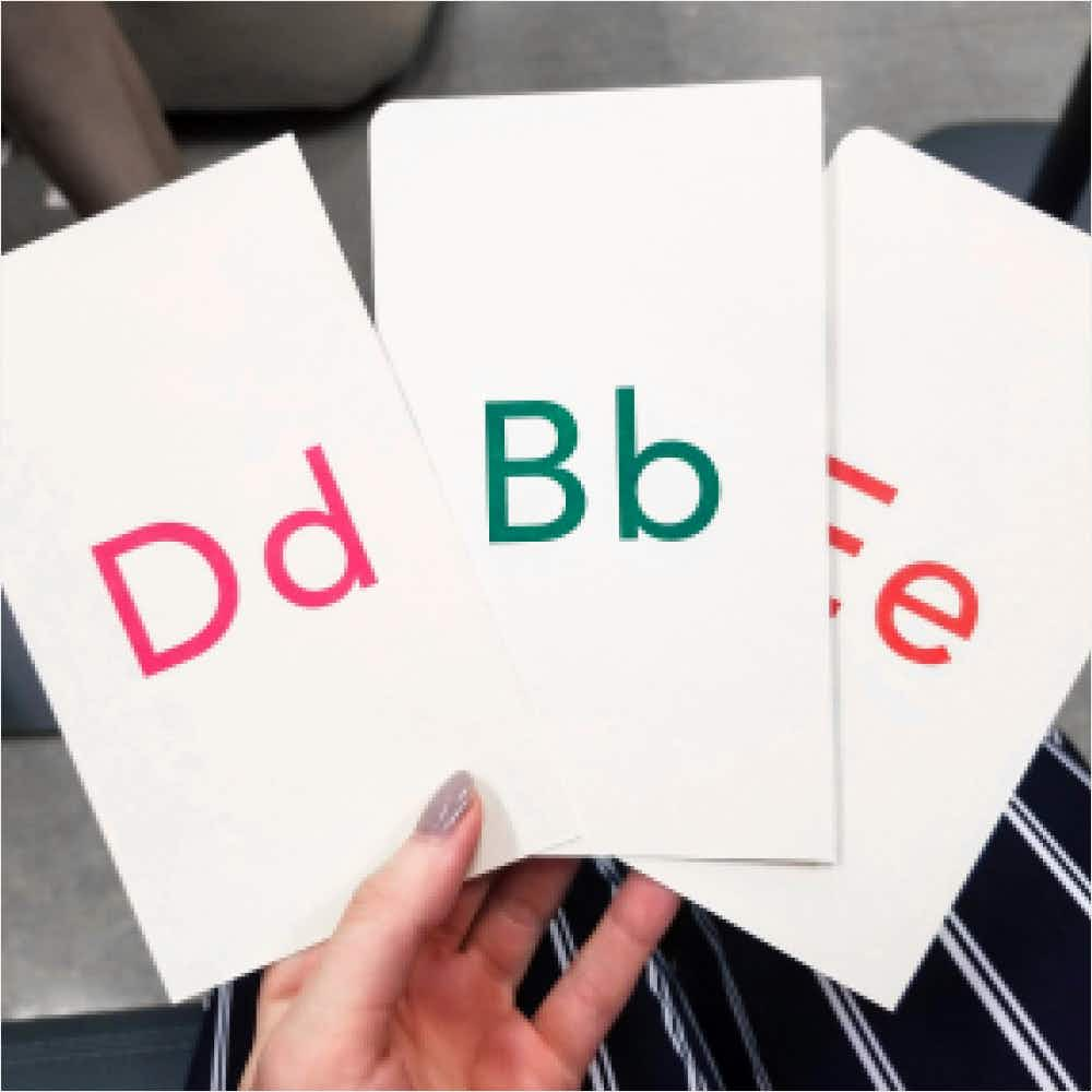 Hand holding cards with letters B, D, and E