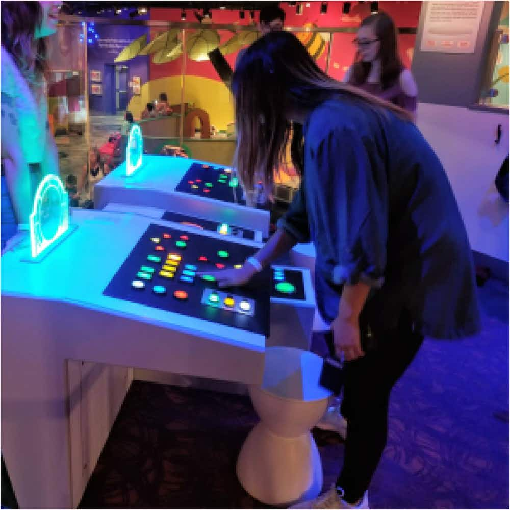 Girl using spaceship control panel at Strong Museum of Play